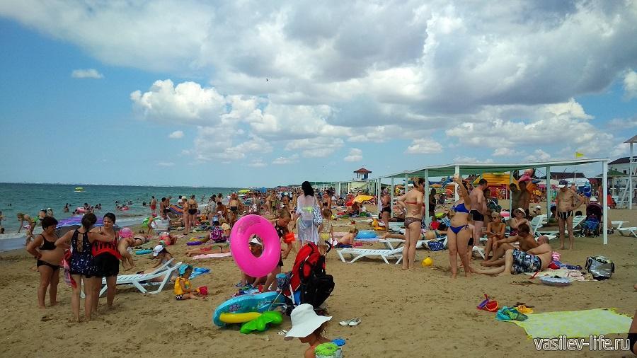 На пляже много людей